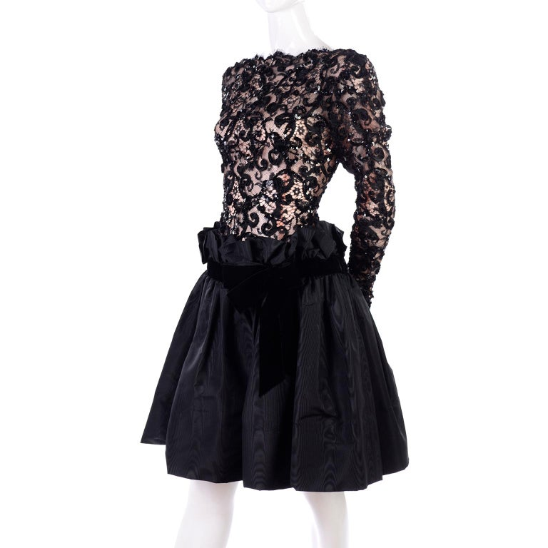 This is a gorgeous Bob Mackie vintage black dress from the 1980's. The lace illusion bodice has a tan lining and is adorned with sequins and ribbons, with eyelash scalloped edges. There is a drop paper bag style waist and the skirt portion of the