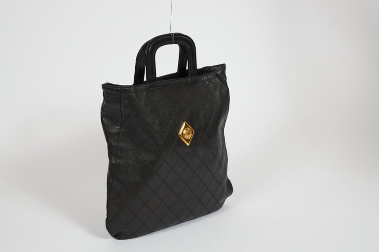 Chanel 80s black leather flat quilted handbag with gold center coin. Comes with generic dust cover.