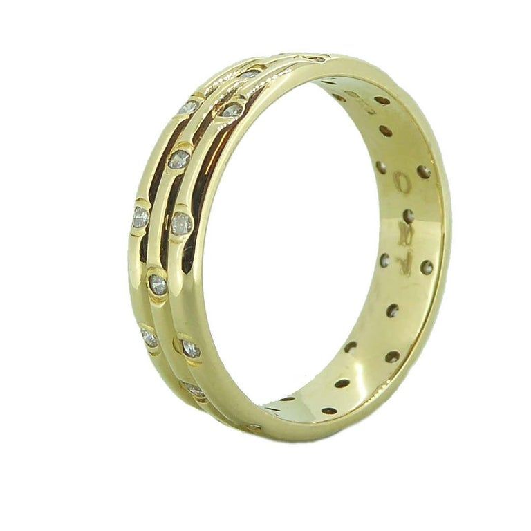 A triple band ring in 18ct yellow gold with 10 diamonds scattered around each of the three bands in rub-over settings. The effect creates a pretty wedding ring which looks just as stunning worn on its own as it would be a diamond engagement ring.