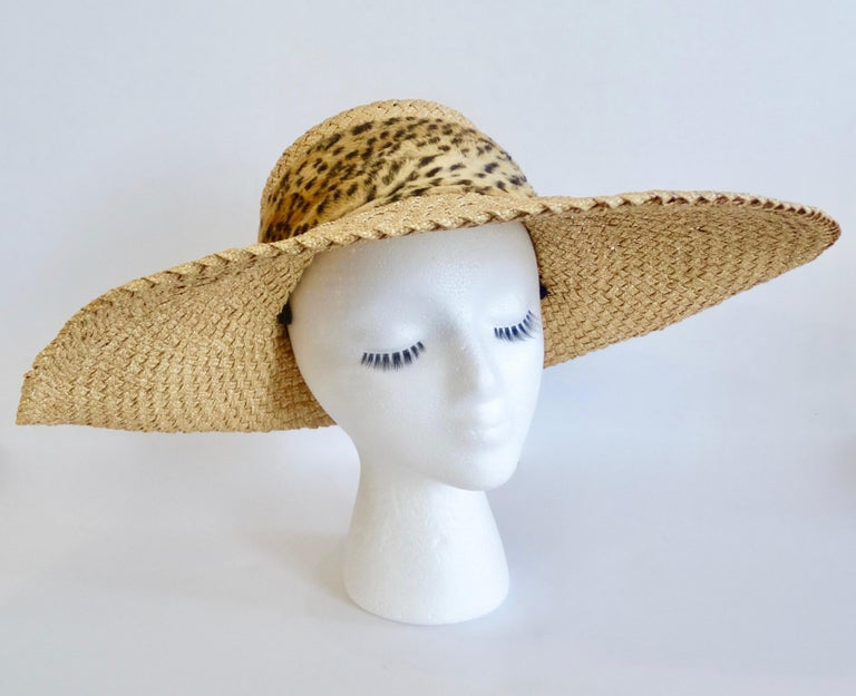 Make a fashion statement with this amazing Whittall & Shon hat! Circa 1980s, this straw hat features a wide asymmetrical propped brim and a faux fur cheetah print band. Chic, timeless and fabulous! This sun hat is sure to turn heads on your next