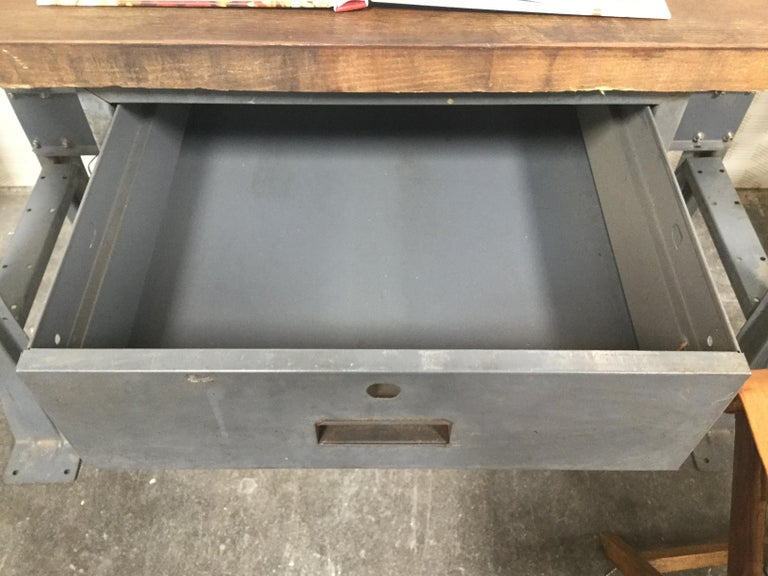 1980s work table with dark wood paneled tabletop. Comes with working storage drawer. Painted grey/blue metal legs. Great for any type of art studio, writers desk, workshop or sewing table, to name a few.