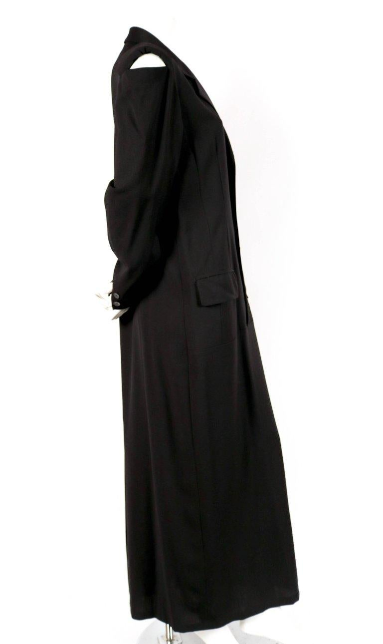 Black long men's style wool dress with cutout shoulders designed by Yohji Yamamoto dating to the 1980's. Labeled a size 'M'. Intended to have a loose oversized fit. Approximate measurements: shoulder 17.75