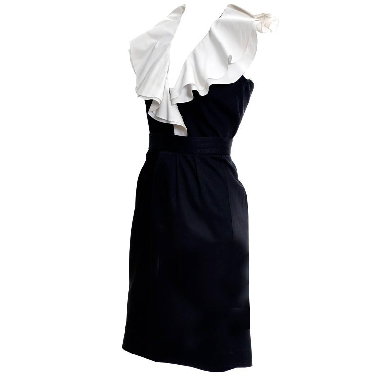 This is a fun black cotton 2 piece YSL dress with a pretty double layer of white ruffles at the neckline. This vintage outfit from Yves Saint Laurent includes a button front sleeveless top that is labeled a size 36, and a slim skirt with zipper and