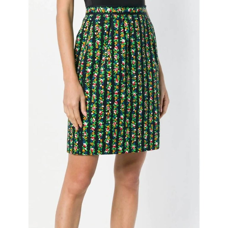 Yves Saint Laurent straight skirt in blue cotton with multicolor floral print. Model with high waist and pleats, welt pockets inserted in the seam, zip and button closure. Length above the knee and lined. Year: 80s  Made in France  Size: 40