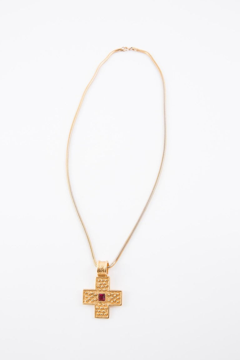 1980s Yves Saint Laurent gold-tone cross necklace featuring a red glass bead, pitted YSL at back cross, a snake chain rolling 60cm length:23.6in. (60cm) Cross 1.5in. (4cm) X 2.3in. (6cm)  In excellent vintage condition  Made in France.  Maxi