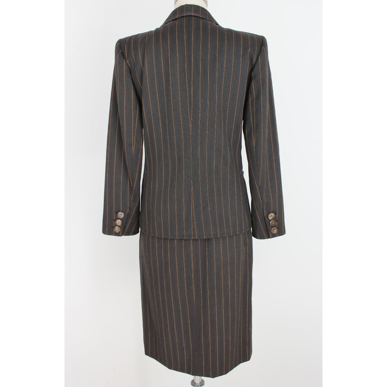 Yves Saint Laurent Rive Gauce vintage woman skirt suit. 100% wool. Pinstriped double-breasted jacket, brown and beige. Gold-colored brooch, 100% silk ysl signature pocket pochette. Lined skirt. 80s. Made in France. Excellent vintage