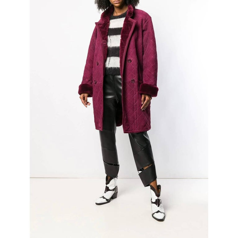 Yves Saint Laurent plum-colored sheepskin coat. Model with stand-up collar and double-breasted closure with buttons. Drop shoulder, long sleeves and decorative stitching.  Years: 80s  Size: 40 FR  Flat measurements  Height: 98 cm Bust: 54