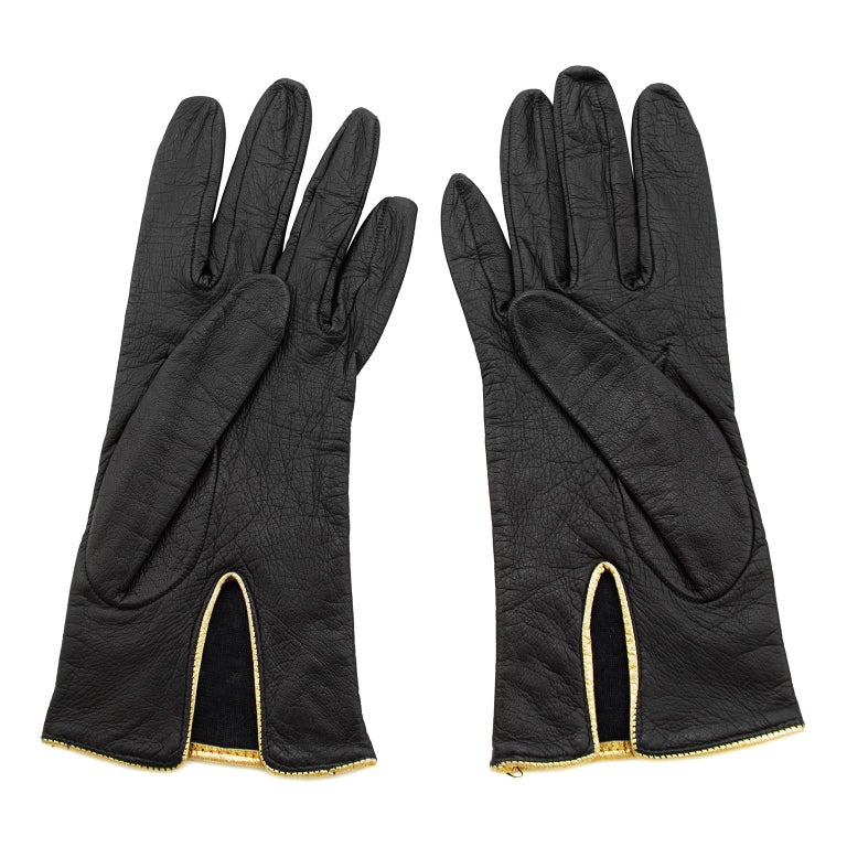 Gorgeous Yves Saint Laurent black leather gloves from the 1980s. Contrasting gold trim and gold studs. Lined in 100% silk. Made in Italy. Excellent vintage condition. Fit like a US 7 which is small.