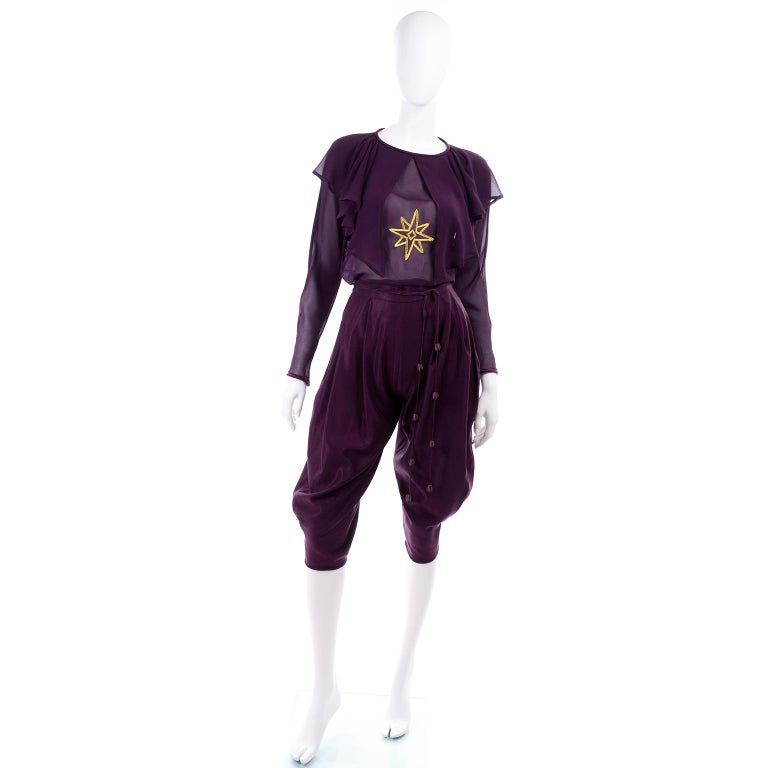 This is a rare vintage Gianni Versace 2 piece deep plum purple outfit from Fall/Winter 1981 that includes a pair of high waist knee length jodhpur style pants or knickers, and a beautiful silk chiffon blouse with a gold star embroidered on the