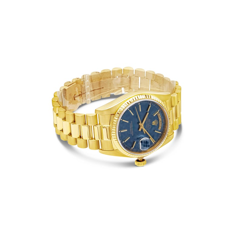 Vintage Rolex watch made in 1982.  Reference 18038.  36mm yellow gold case set with a fluted bezel and sapphire crystal.  Blue sunburst dial with baton hour markers and hands.  Date aperture with cyclops magnifier at 3 o'clock; day aperture at 12