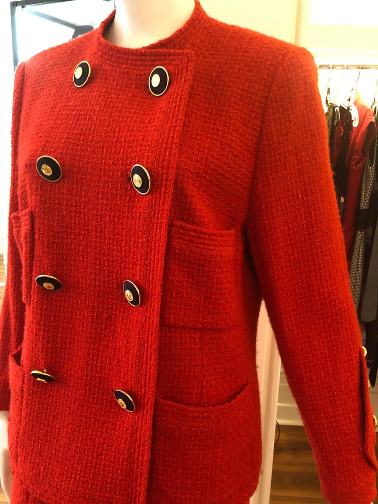 Featured in Emma Baxter-Wright's book Chanel, this red boucle wool suit is from Karl Lagerfeld's first collection for the House of Chanel. The fitted jacket has a double row of gilt buttons, and four pockets, whilst the skirt has a false double