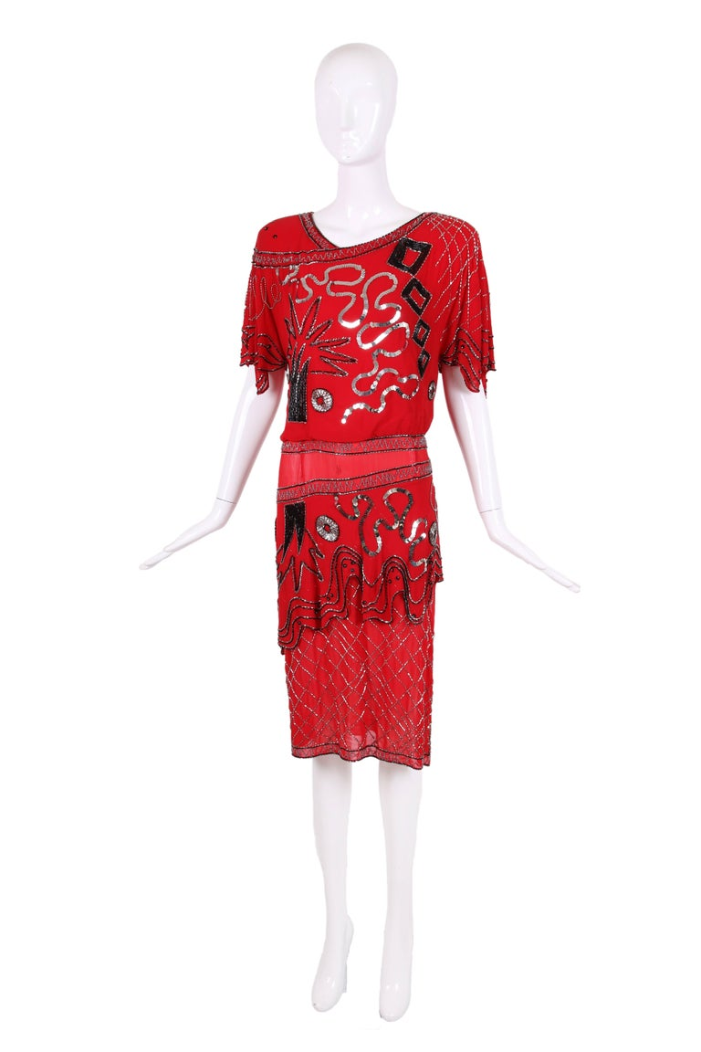 1984 Fabrice red silk cocktail dress with asymmetric pattern of shapes made from black and silver beads and sequins. The dress features a short flounce sleeve, a drop waist with an additional layer of fabric below and a slit at one leg. Lined at the