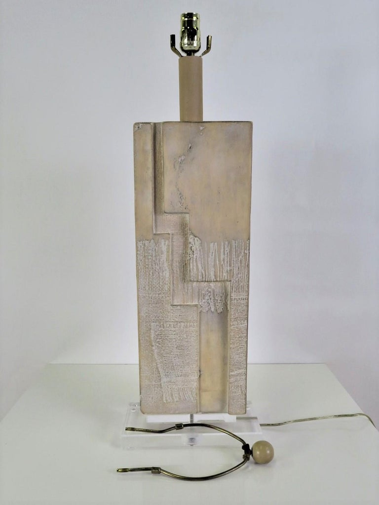 Raised on a lucite rectangular plinth base, this 1980s Lamp has a Brutalist Shaped stacked Stone Slab Form center. Made by Casual Lamps of California, incorporating their favorite look of whitewashed forms. Original wiring and new three level UL