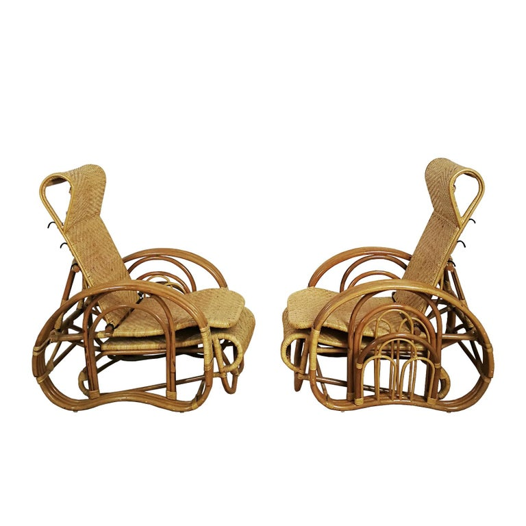 Pair of convertible armchairs in rattan (Malacca cane), adjustable back and sliding footrest, under the seat. Magazine rack on one side. New condition.  Indonesia, c. 1990  Measurement: (W) 66- 70 (with magazine rack) x (D) 75- 100 (Back down)-