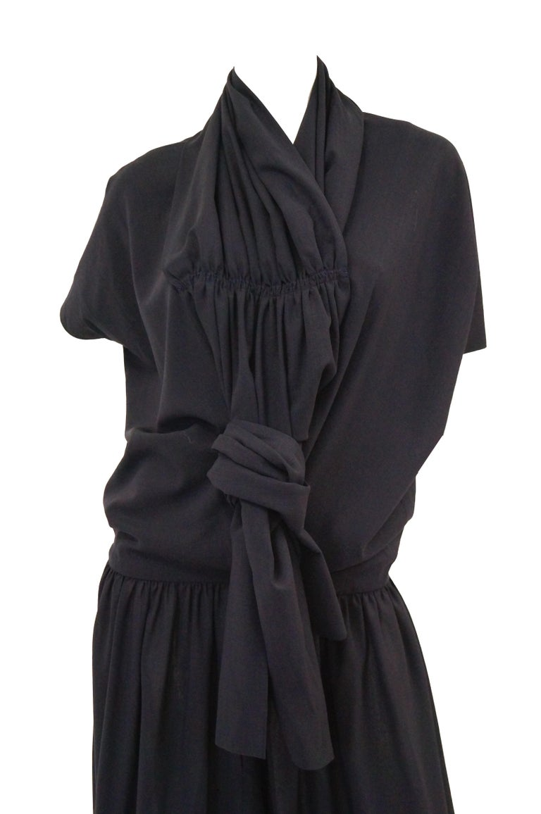 Amazing dark navy blue light weight wool dress and coordinating hat by Yohji Yamamoto! The dress has a loose drop waist silhouette with lightly pleated skirt, short sleeves, and a deep V - neckline openings both in the front and back of the dress.