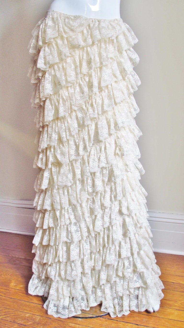 An incredible maxi skirt from the early collections of Alexander McQueen covered in rows and rows of angled cascading off white lace ruffles. The skirt is slightly longer in the back draping beautifully.  It closes with a matching side invisible