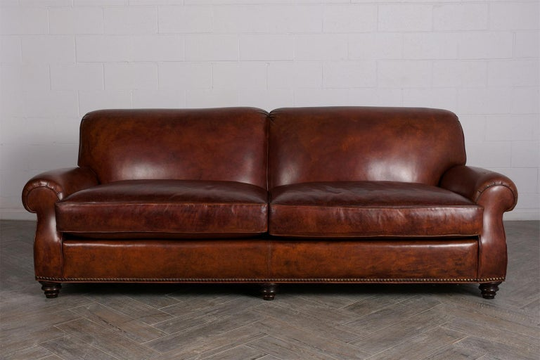This Vintage Leather Sofa is in great condition and is upholstered in its original rich brown color leather in great condition and has a beautiful patina finish. This sofa also features round armrests, two large seat cushions with single piping