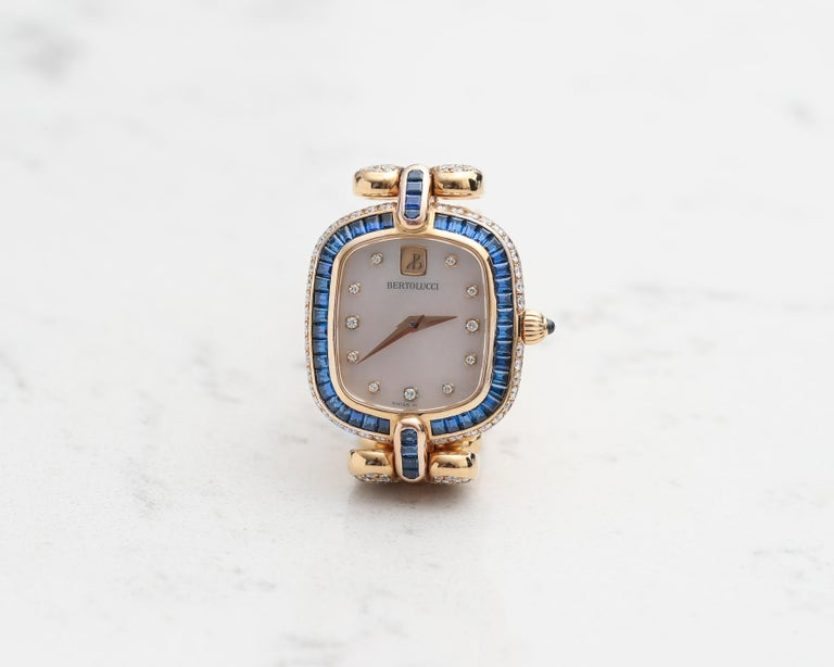 1990s Bertolucci Womens Wristwatch Featuring Mother of Pearl Diamond Dial, crafted in 18 Karat Yellow Gold   Diamond Details - 3 Carats, E-F Color, VVS Clarity, Round Brilliant Cut Sapphire Details - 3 Carats, all custom cut Baguette diamonds   Fits