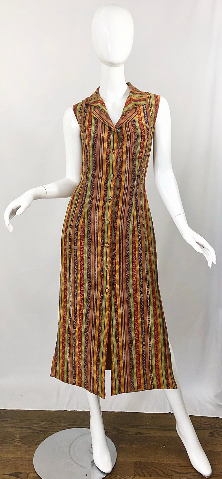 Stylish vintage early 90s warm color vertical striped Aztec themed midi shirt dress! Features warm colors of orange, yellow, green, purple, maroon and yellow throughout. Adjustable tie at back waist can adjust to fit. Very well made, obviously by a