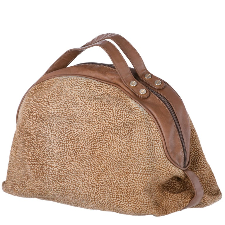 Borbonese half-moon leather and suede handbag, in partridge eye pattern. Brown leather handles, golden metal details, brown interior, double-slider zip closure with tie.  The bag shows signs of wear in the leather parts, in the suede part and a pen