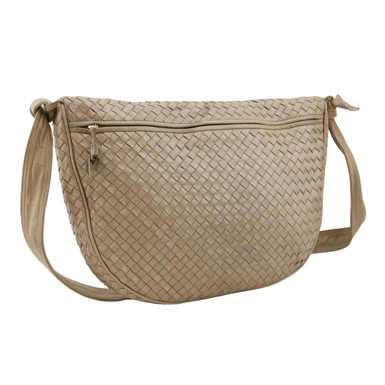 Beautiful 1990s Bottega Veneta hobo bag. Taupe intrecciato leather with matching taupe leather crossbody strap. Strap features monochromatic top stitching and knot details. Large slit pocket with zipper on front and small slit pocket with zipper on