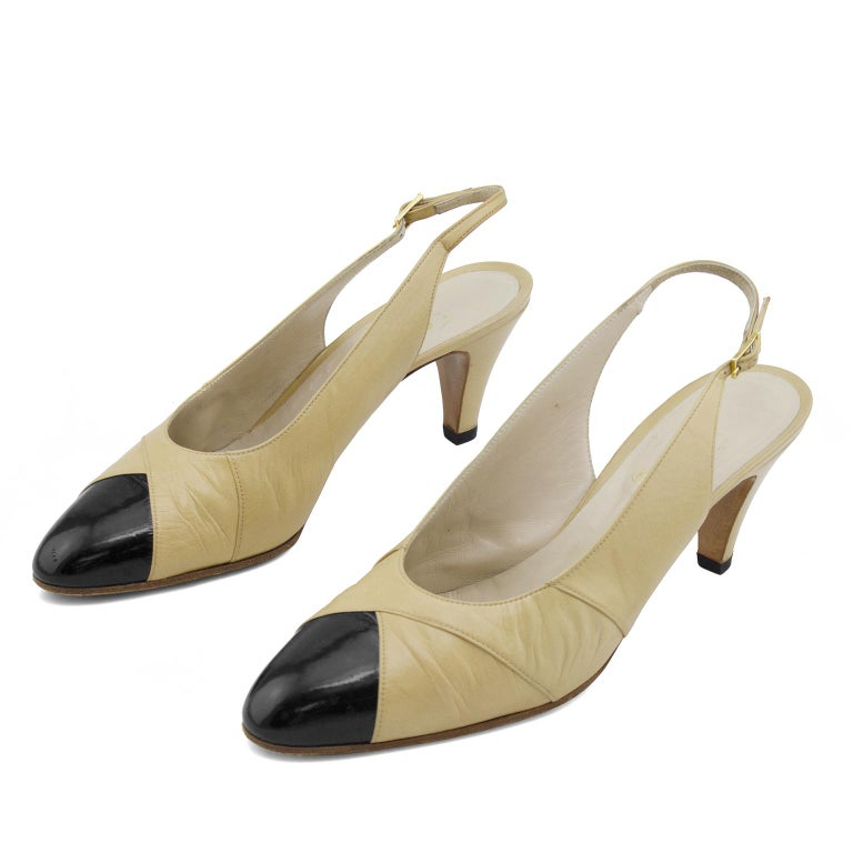 Early 1990s Beige wrapped leather Chanel sling backs. Contrasting black patent leather cap toe. Beige and black is the most classic and iconic Chanel colour combination. Gold-tone branded buckle at sling back. Black heel caps. Metallic gold brand