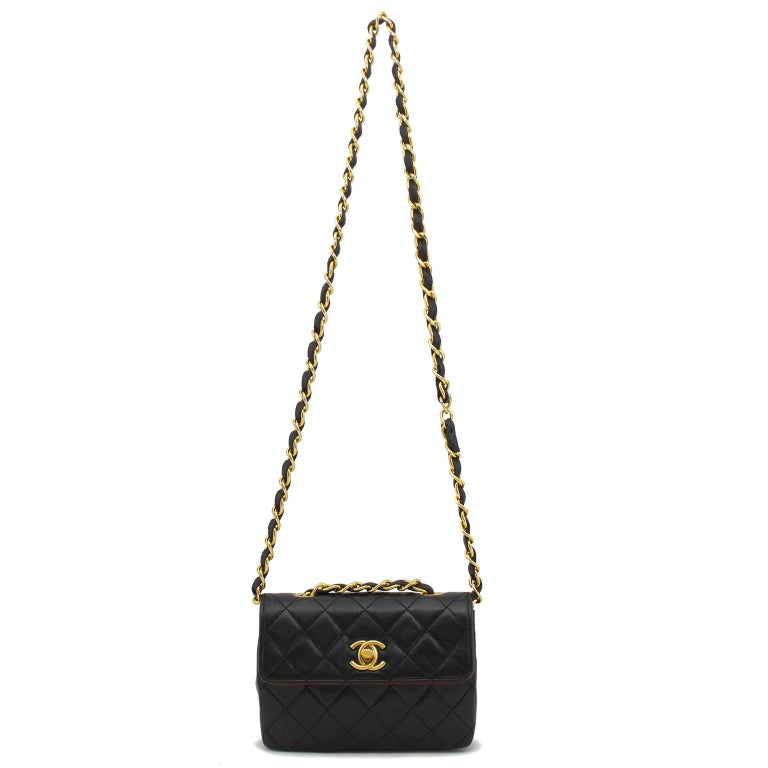 1990s black quilted leather vintage Chanel classic mini flap bag with gold-tone hardware, single chain-link and leather shoulder strap, CC gold-tone turn-lock closure at front flap. Includes dust bag and authenticity card. Excellent vintage