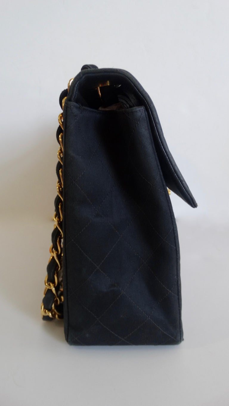 Complete your Chanel collection with this amazing classic single flap! Circa 1990s, this timeless Chanel is crafted from soft black satin and features the signature quilted stitching, gold hardware and a pouch pocket on the back face. Includes dual