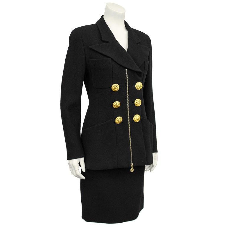 1990s Chanel black wool skirt suit. Double breasted jacket features an exaggerated collar, large woven gilt metal buttons, two small and two large patch pockets and a centre gold zipper. Zipper opens from bottom and can allow for a little more room