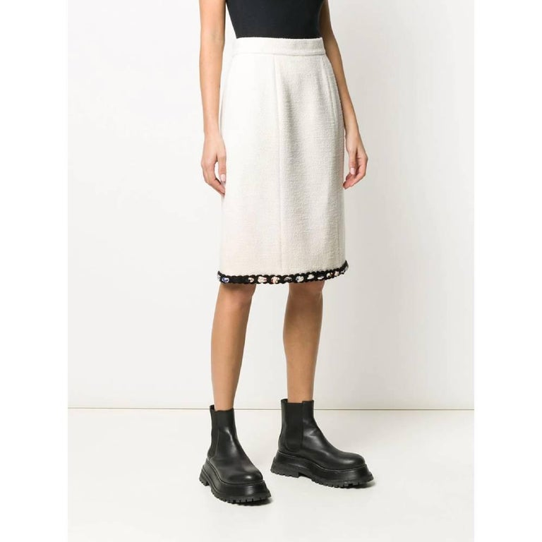 Chanel ivory wool blend skirt. Straight model with high waist and decorated hem. Closure with hooks and zip on the back. Above the knee length and straight bottom.  Years: 90s  Made in France  Size: 40 FR  Flat measurements  Lenght: 62 cm  Waist: 34