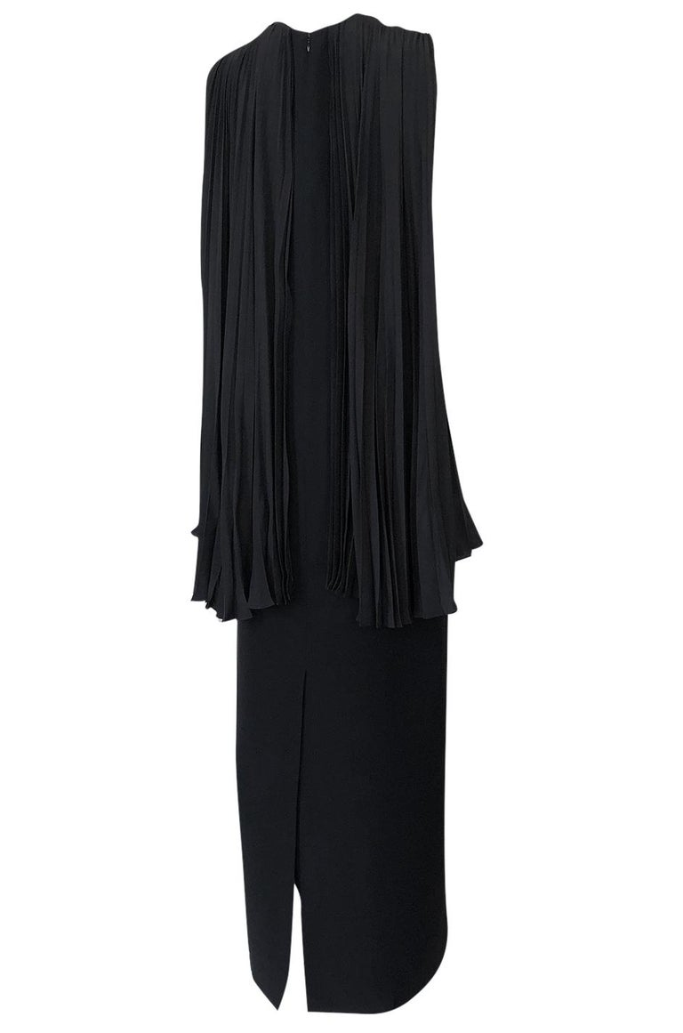 This is a beautiful black dress from the Christian Dior label that showcases the restraint and elegance that the best of the brand's work has always displayed. The main dress under the cape is cut in one long and lean line. This simple sheath