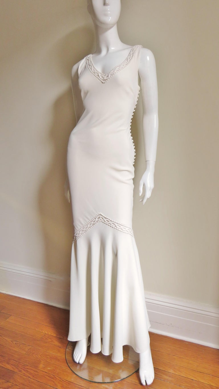 A stunning off white silk gown from Christian Dior.  It has a plunging neckline front and back bordered with an 1 1/2