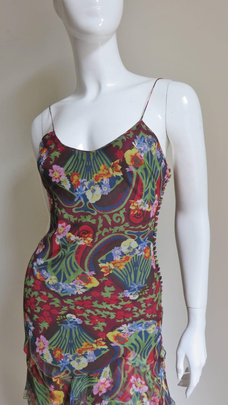 A gorgeous silk dress by John Galliano for  Christian Dior in brightly colored flowers on a navy and burgundy background.  The spaghetti strap bodice is semi fitted to the hips and adorned on one side with almost 3 dozen Dior signature self covered