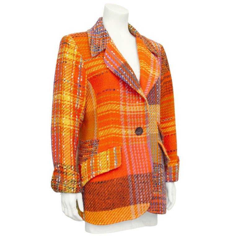 Christian Lacroix equestrian style blazer from the 1990s. Patchwork orange, yellow and purple tweed with a distorted plaid pattern throughout. Notched collar and single carved wood button. Three flap pockets, two on the left and one on the right.