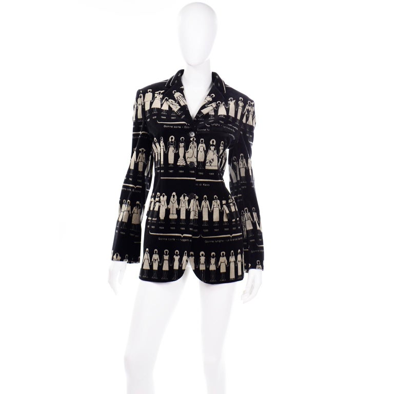 This is a really fabulous deadstock vintage Moschino black velvet blazer in a fashion history print that features clothing from the 1920's through 1997.  The timeline print shows women holding hands in different dresses and outfits. This blazer has