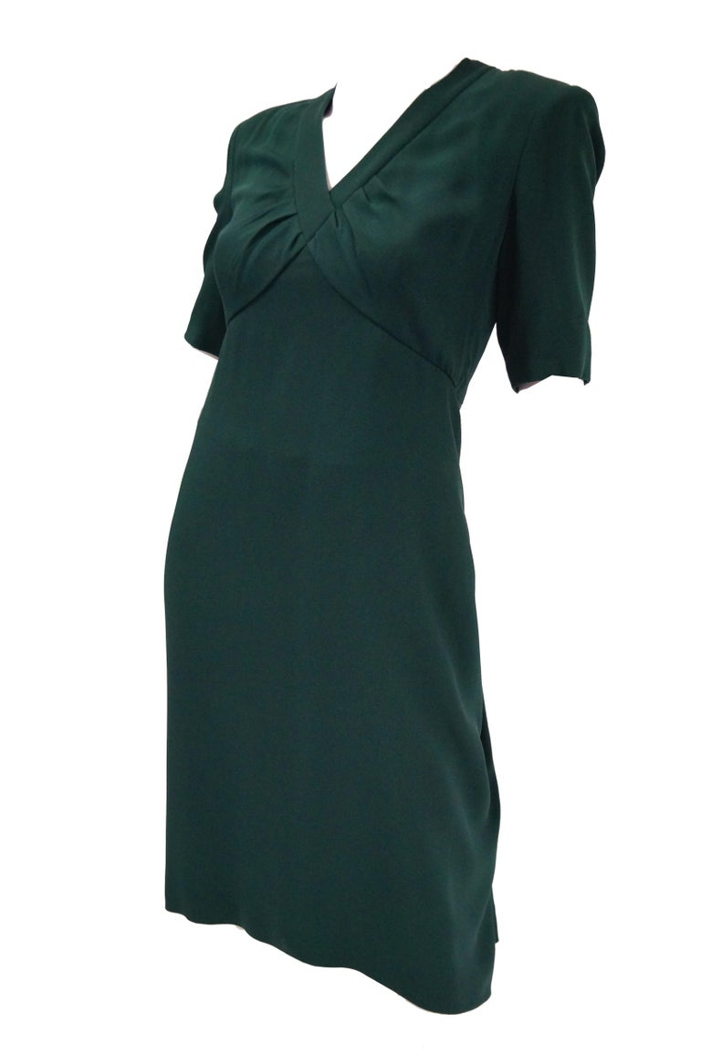 Elegant and understated haute couture dress by Gianfranco Ferre for Christian Dior. The forest green dress is knee length, with sleeves that fall just above the elbow, and a V - neck collar. The dress has a loose sheath silhouette with empire waist