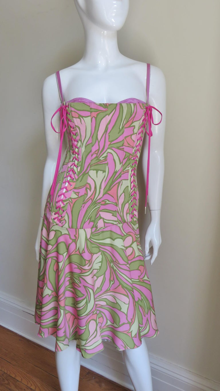 A beautiful pinks and greens geometric stretch silk print dress from Dolce & Gabbana.  It is fitted through the dropped waist torso and boned vertically throughout.  There is an attached matching pink fully adjustable bra which peeks out of the top