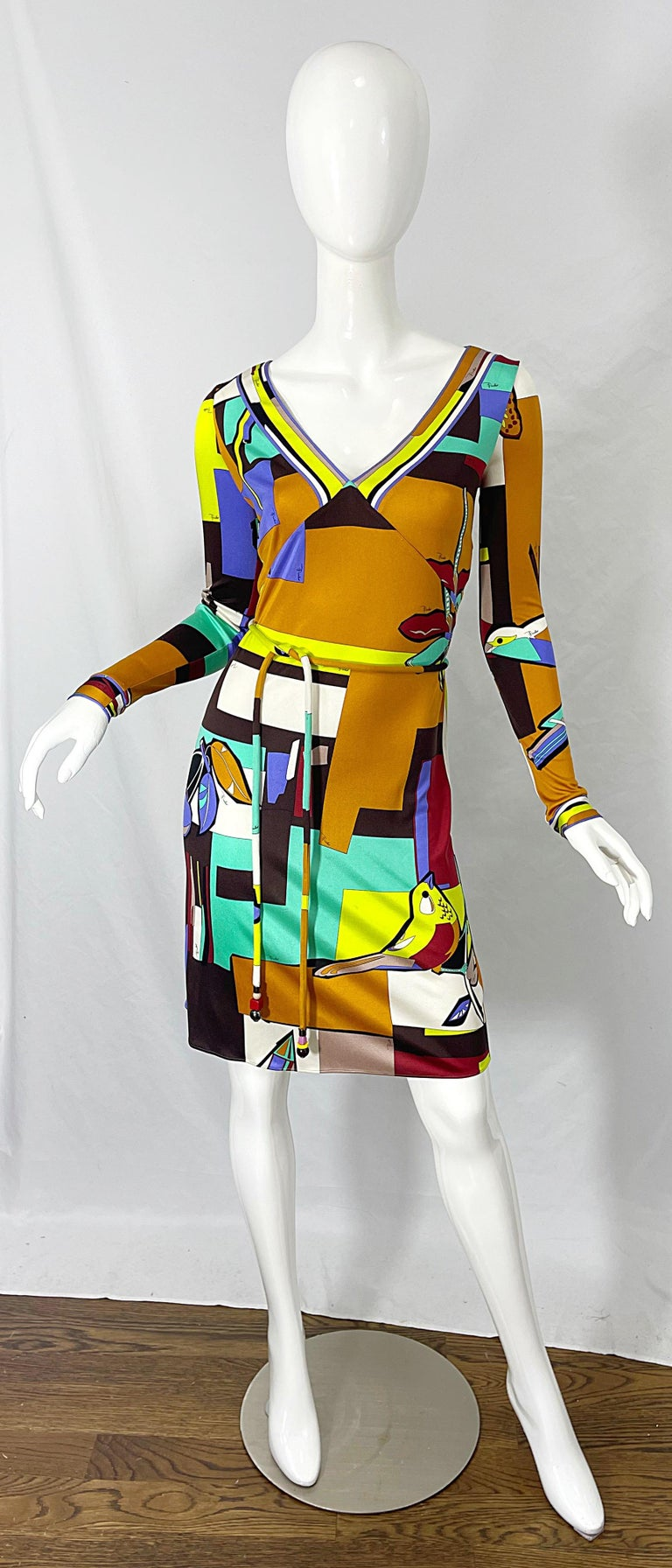 Amazing 1990s EMILIO PUCCI novelty bird, butterfly, and dragonfly print silk jersey long sleeve belted dress ! Features a tailored v-neck bodice with a slinky skirt. Vibrant colors of turquoise blue, purple, neon green, white, black and terra cotta.