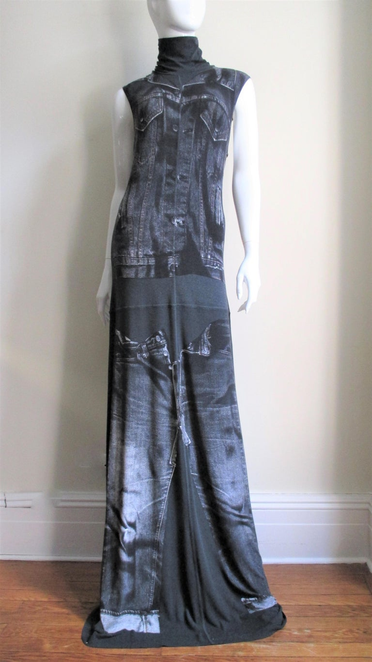 A great maxi dress from Jean Paul Gaultier in a black jersey with a trompe l'oeil jean jacket and jeans screen printed on the front and back.  It has a stand up collar and skims the body then flares to the hem.  It comes with fabulous separate