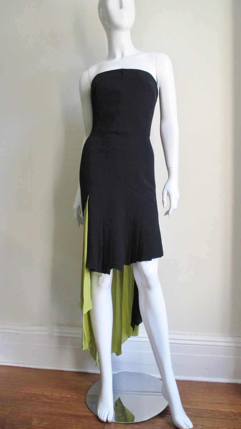 A silk bustier color block dress in black and muted lime green with a high low asymmetrical pleated hemline from Gianni Versace.  The dress has a separate inner boned zippered satin corset for support. It is fitted through the hips then falls in