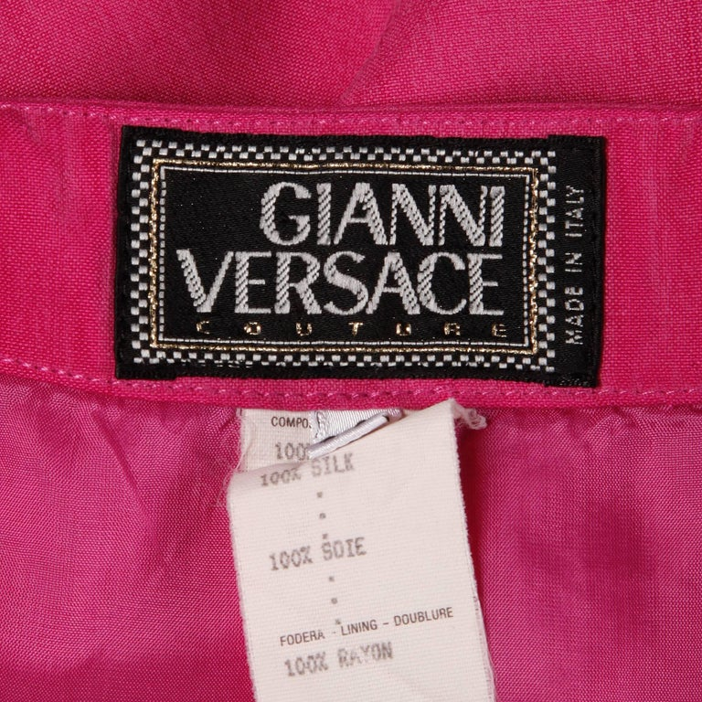 Bright pink silk skirt with iconic medusa buttons by Gianni Versace.  Details:   Fully Lined Button Front Closure Marked Size: 4 Estimated Size: XS-S Color: Bright Pink Fabric: 100% Silk Label: Gianni Versace Couture  Measurements:   Waist:
