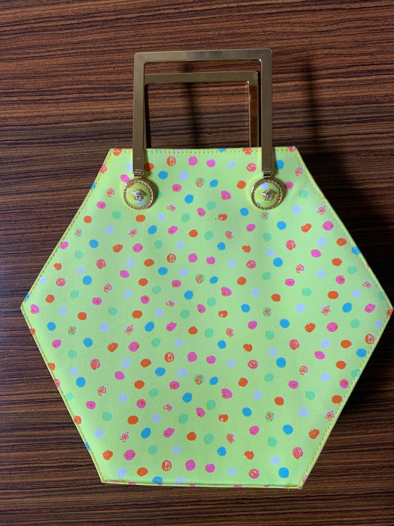 Super fun vintage 1990s Versace yellow hexagonal shape hand bag with multicolored painterly polka dot pattern. Gold tone Versace Medusa hardware fastens gold tone rectangular handles. Gold tone Medusa pull at zip top.  An amazing example from the