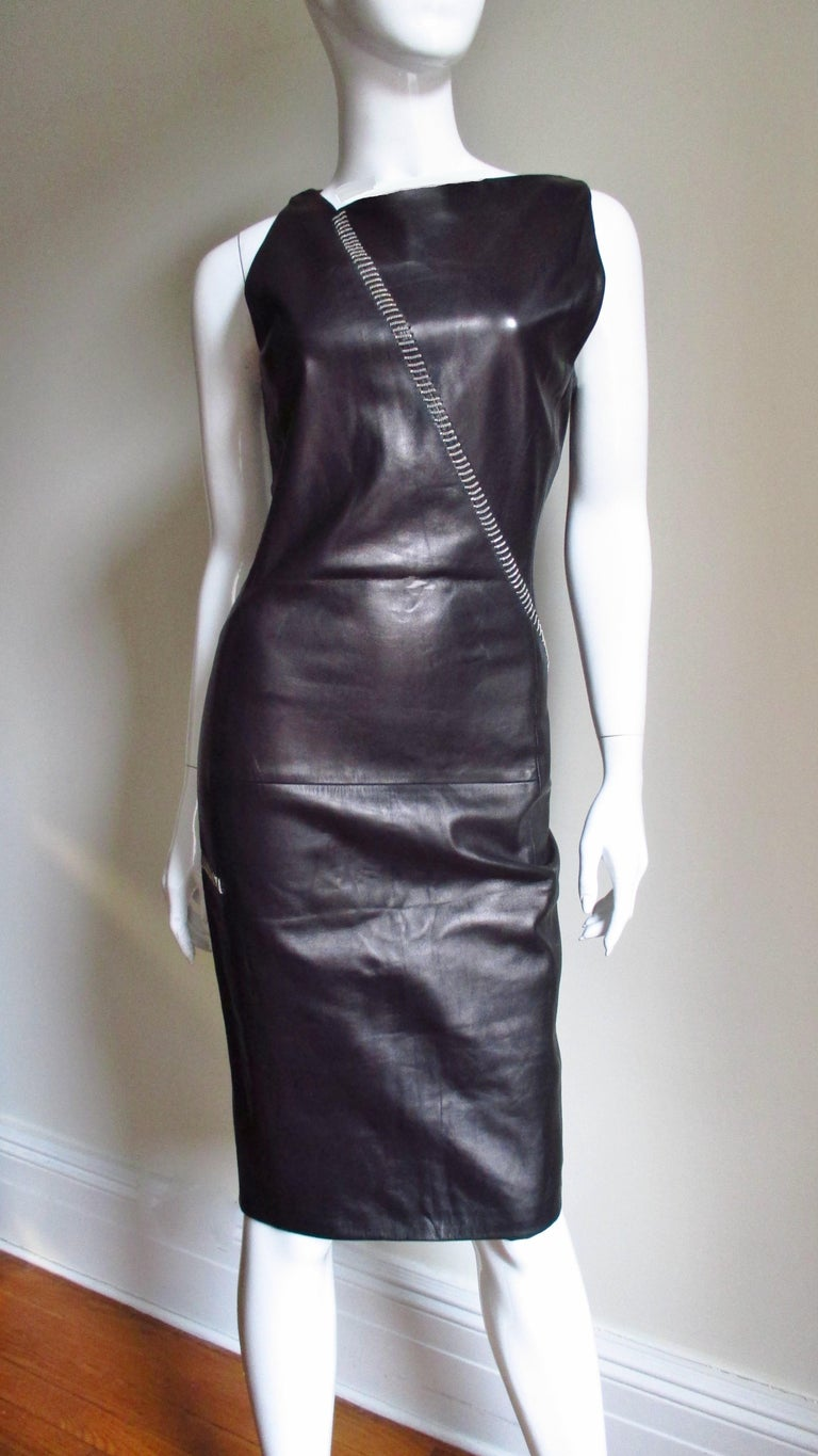 A fabulous soft supple black leather dress from Gianni Versace.  It is fitted with an asymmetrical neckline with a chain starting at one side crossing the front to the hip then wrapping around the dress to the back across the hips.  It is fully