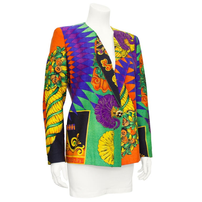 Gorgeous 1990s Gianni Versace jacket. Orange, green, yellow, and black all over abstract print. Collarless with folded lapel and black top stitching details. Single large round gold tone button embellished with black, white and amber rhinestones.
