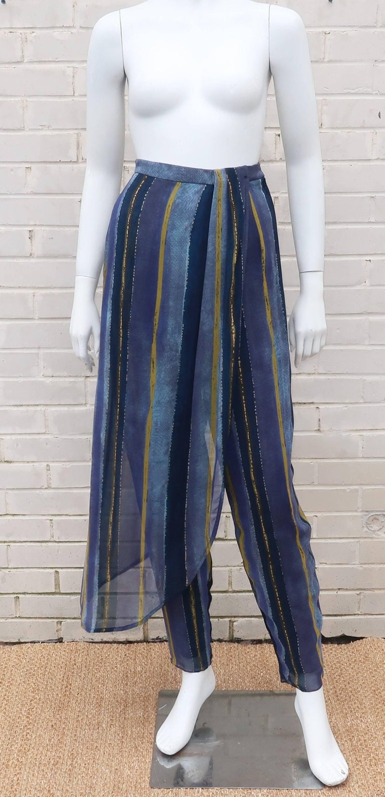 This Giorgio Armani pant design is teeming with exotic inspiration and a sensual silhouette.  The fully lined silk pants button and zip at the side with hidden pockets, a sarong style waistband and a tapered leg.  The abstract striped print in