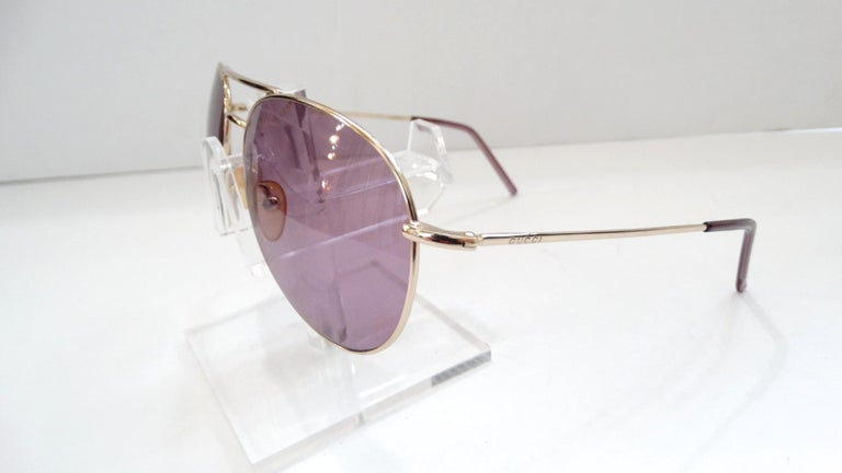 In Need Of A New Favorite Pair Of Sunnies? These 1990s Gucci aviators are perfect! These dead stock Gucci sunglasses feature silver hardware and semi clear purple tinted lenses. Includes purple temple covers and is stamped
