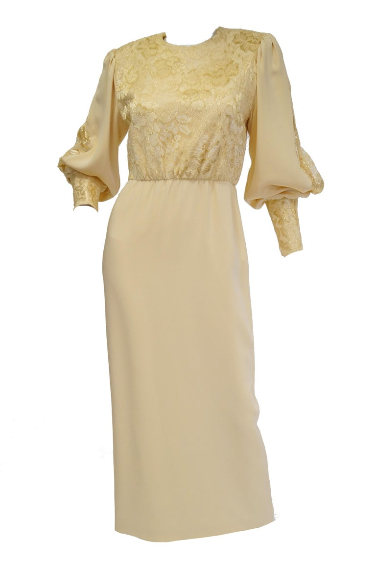 A dreamy ivory/cream evening dress of couture quality design and execution. The dress is maxi length, with long sleeves, an A - line silhouette, and a somewhat loose bodice. The bodice is entirely covered in intricate floral lace, and has a high