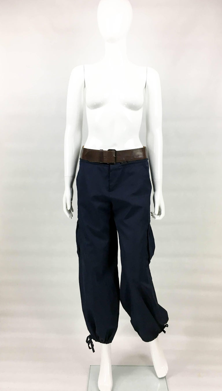Vintage Jean Paul Gaultier Navy Blue Nylon Cargo Pants. This really cool piece by Jean Paul Gaultier dates back from the 1990's. Made in navy blue nylon, the pants feature a detachable brown belt. With drawstrings to cuffs, they have sash pockets to