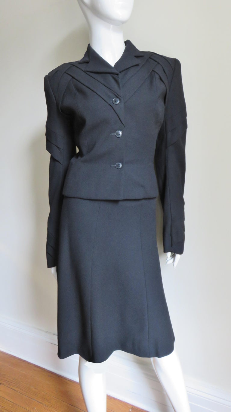 A gorgeous black wool suit with a twist by John Galliano.  It consist of a hip length single breasted jacket with small lapels and beautiful thatched tucking detail at the center front/back, padded shoulders, upper and lower arms creating fabulous