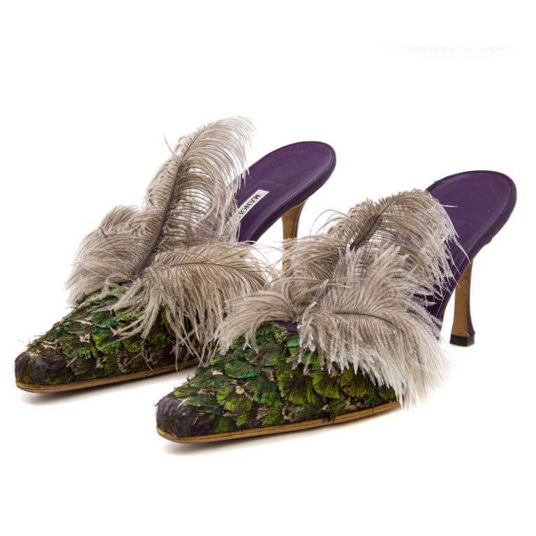 Birds of a feather! These Manolo Blahnik high heeled mules look like a pair of exotic birds for your feet. The pointed toe box is covered in iridescent green and purple feathers in an overlapping formation and finished with a plume of 3 grey long